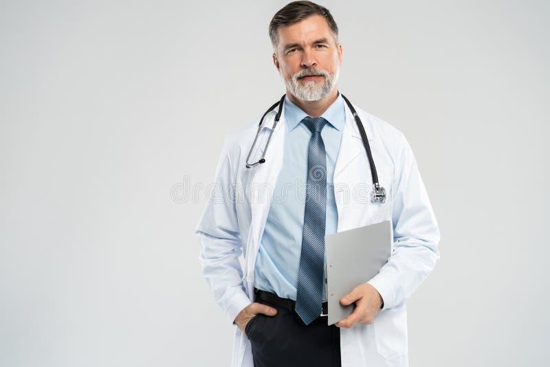 Εύθυμος ώριμος γιατρός που θέτει και που χαμογελά στη κάμερα, την υγειονομική περίθαλψη και την ιατρική στοκ εικόνα με δικαίωμα ελεύθερης χρήσης