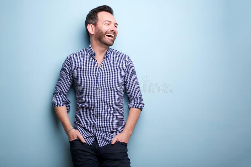Εύθυμο άτομο με την τοποθέτηση γενειάδων ενάντια στον μπλε τοίχο στοκ εικόνες