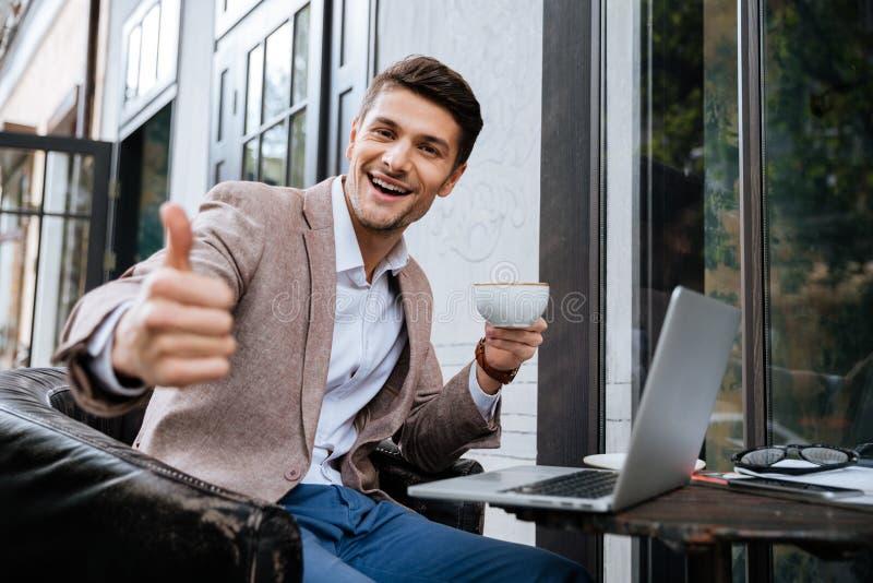 Εύθυμο άτομο με το lap-top που παρουσιάζει αντίχειρες στον υπαίθριο καφέ στοκ φωτογραφία