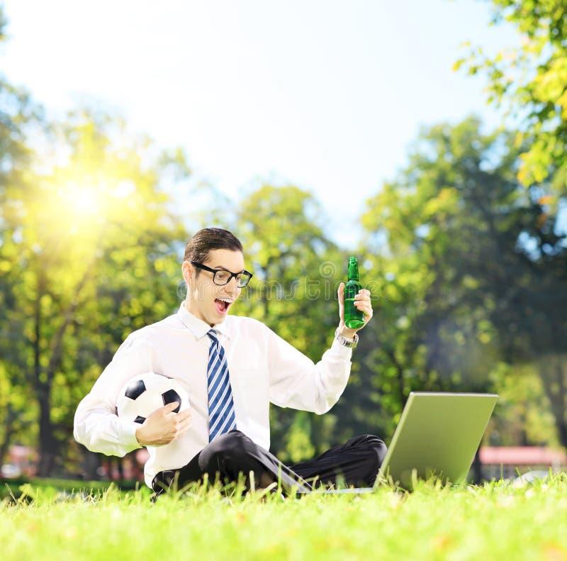 Εύθυμο άτομο που κάθεται σε ένα πράσινο ποδόσφαιρο προσοχής χλόης σε ένα lapt στοκ φωτογραφία