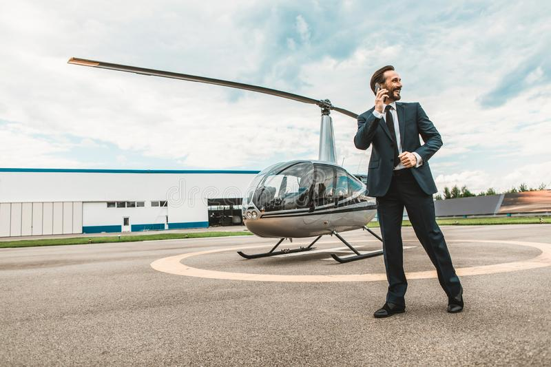Εύθυμο άτομο που μιλά στο τηλέφωνο ενώ όντας κοντά στο ελικόπτερο στοκ φωτογραφίες με δικαίωμα ελεύθερης χρήσης