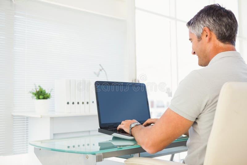 Εύθυμο άτομο που χρησιμοποιεί το lap-top του στο γραφείο στοκ φωτογραφίες με δικαίωμα ελεύθερης χρήσης