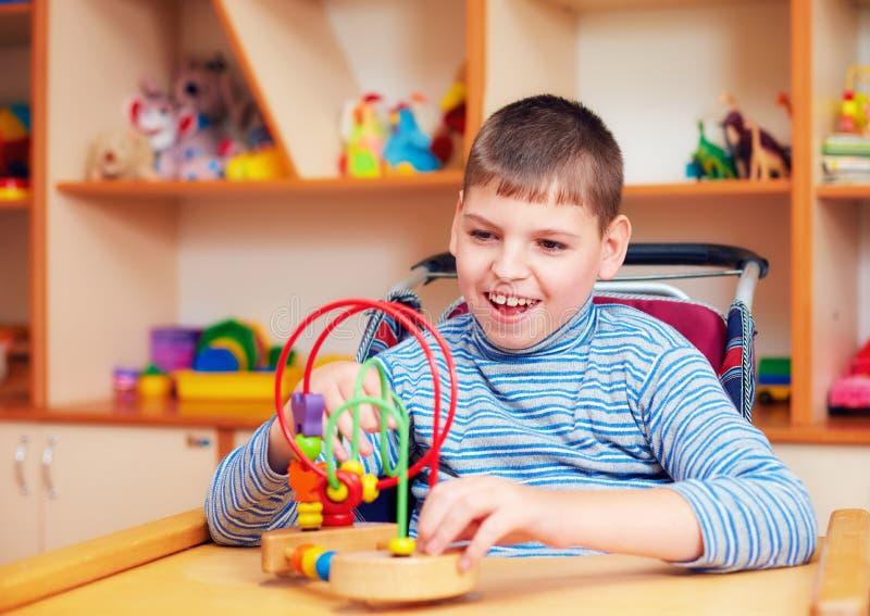 Εύθυμο αγόρι με ειδικές ανάγκες στο κέντρο αποκατάστασης για τα παιδιά με ειδικές ανάγκες, που λύνουν το λογικό γρίφο στοκ φωτογραφία