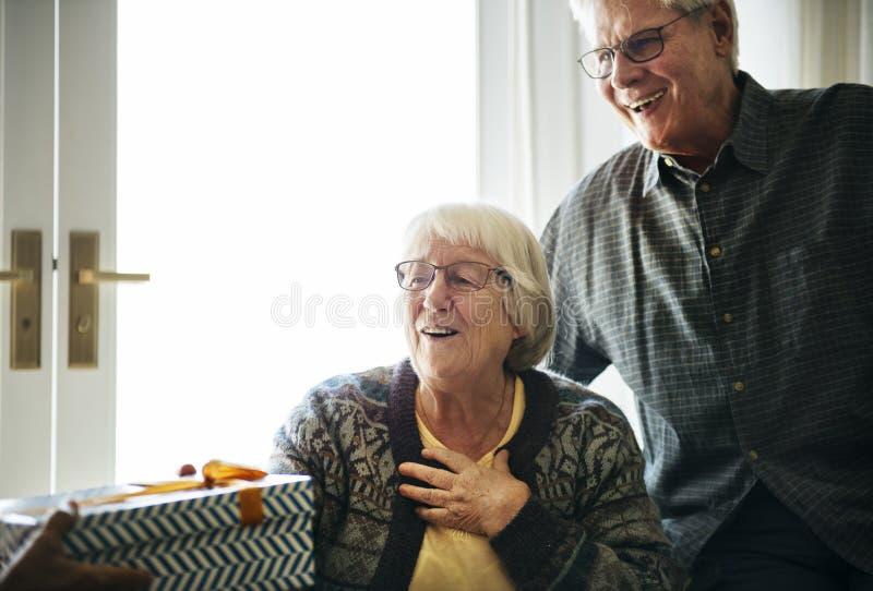 Εύθυμο ανώτερο ζεύγος που λαμβάνει ένα κιβώτιο δώρων στοκ φωτογραφίες