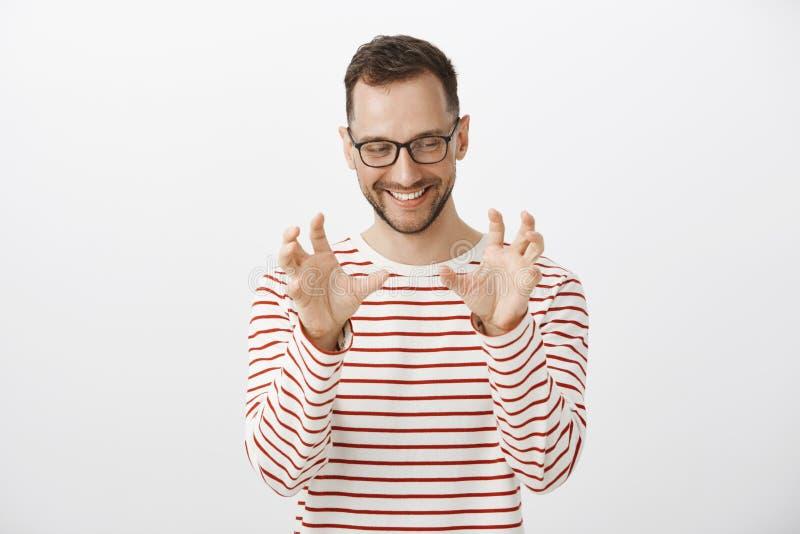 Εύθυμο αστείο ευρωπαϊκό αρσενικό πρότυπο στο ριγωτά πουλόβερ και τα γυαλιά, που κοιτάζουν κατά μέρος κοκκινίζοντας και χαμογελώντ στοκ εικόνες με δικαίωμα ελεύθερης χρήσης