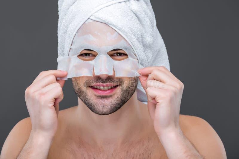 εύθυμο γενειοφόρο άτομο με τη μάσκα πετσετών και κολλαγόνων, στοκ φωτογραφίες με δικαίωμα ελεύθερης χρήσης
