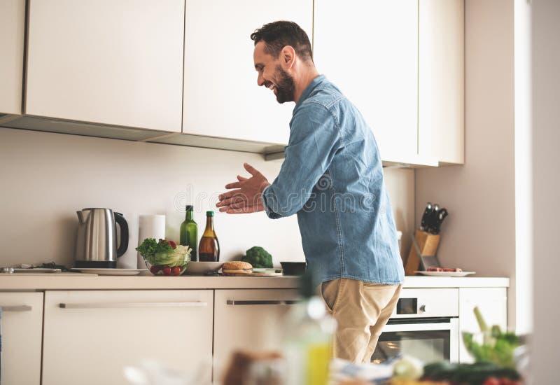 Εύθυμο γενειοφόρο άτομο που στέκεται στην κουζίνα και που τρίβει τα χέρια του στοκ φωτογραφία