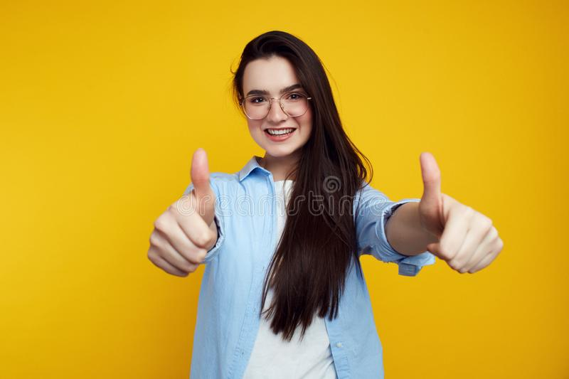 Εύθυμο ελκυστικό θηλυκό που παρουσιάζει αντίχειρες που απομονώνονται επάνω στον πορτοκαλή τοίχο στοκ εικόνες με δικαίωμα ελεύθερης χρήσης