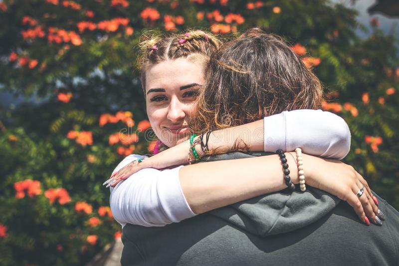 Εύθυμο ερωτευμένο αγκάλιασμα ζευγών χαμόγελου στη φύση σε ένα όμορφο υπόβαθρο λουλουδιών Νησί του Μπαλί στοκ εικόνα