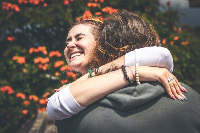 Εύθυμο ερωτευμένο αγκάλιασμα ζευγών χαμόγελου στη φύση σε ένα όμορφο υπόβαθρο λουλουδιών Νησί του Μπαλί στοκ φωτογραφίες