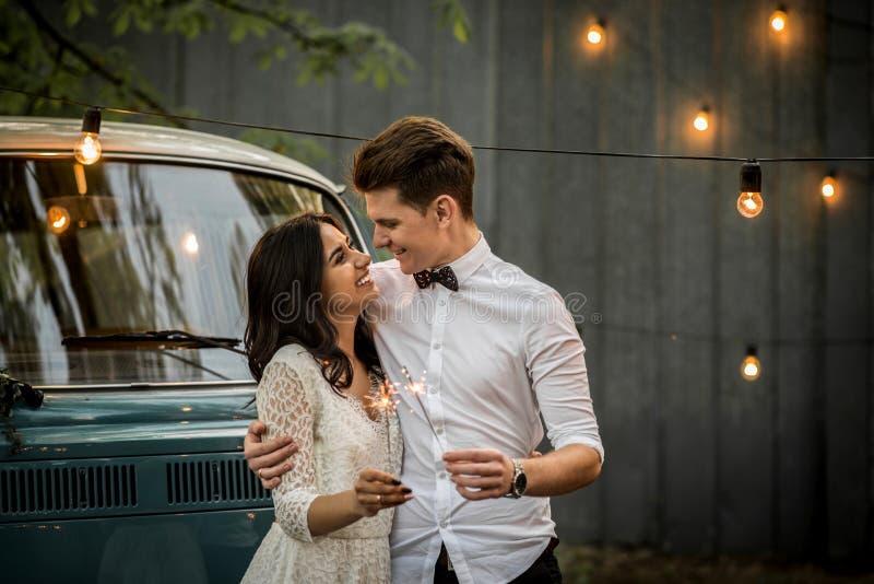 Εύθυμο ευτυχές νέο ζεύγος που αγκαλιάζει κοντά αναδρομικό σε έναν minivan Κινηματογράφηση σε πρώτο πλάνο στοκ φωτογραφία