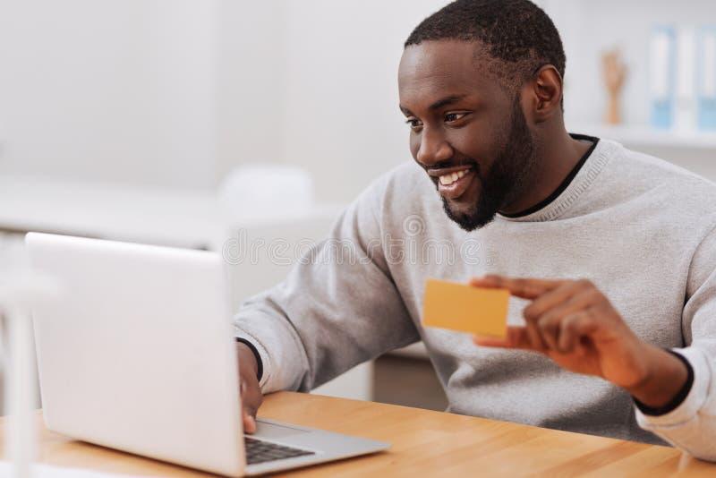 Εύθυμο ευχάριστο άτομο που κάνει μια σε απευθείας σύνδεση πληρωμή στοκ φωτογραφία