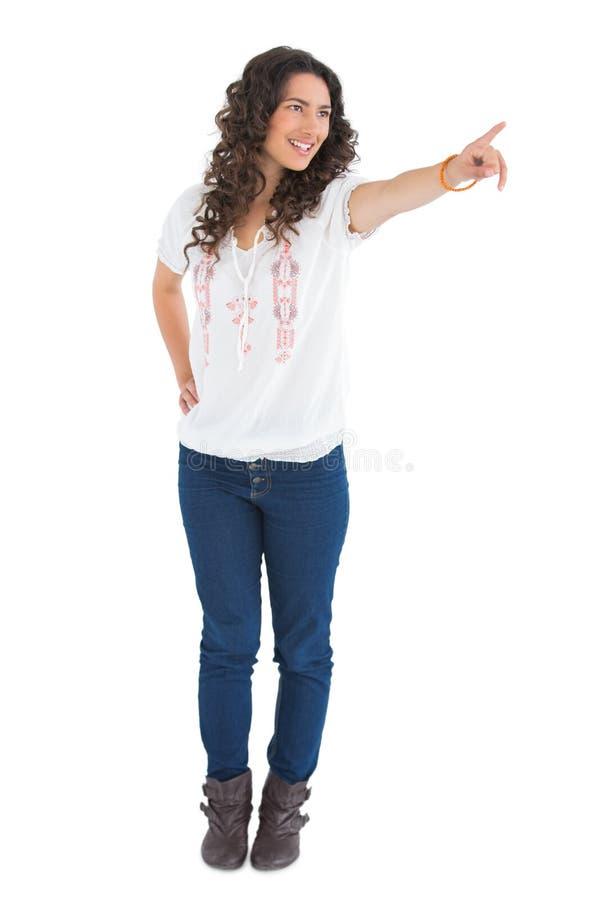Εύθυμο ελκυστικό brunette που φορά την υπόδειξη περιστασιακών ενδυμάτων στοκ φωτογραφία με δικαίωμα ελεύθερης χρήσης