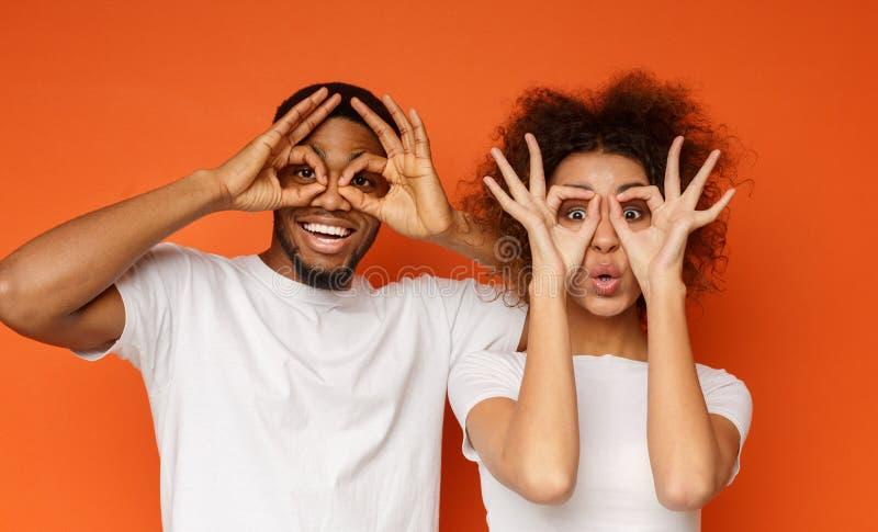 Εύθυμο ζεύγος ερωτευμένο έχοντας τη διασκέδαση και κρατώντας τα δάχτυλα κοντά στα μάτια στοκ φωτογραφία με δικαίωμα ελεύθερης χρήσης
