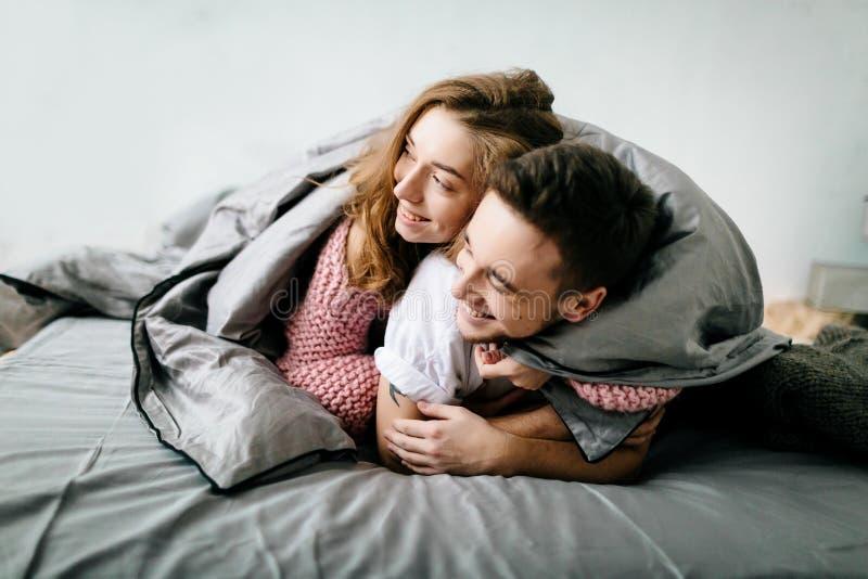 Εύθυμο ζεύγος κάτω από το coverlet στο κρεβάτι τους _ Μαλακή εστίαση στο κορίτσι στοκ φωτογραφία