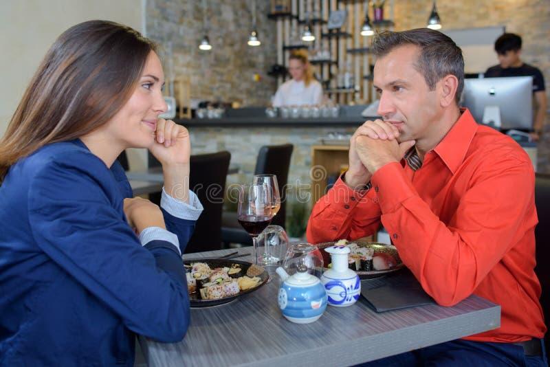 Εύθυμο ζεύγος που έχει το μεσημεριανό γεύμα στον κήπο ξενοδοχείων στοκ εικόνες