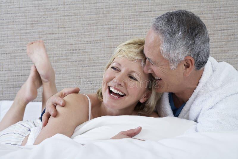 Εύθυμο ζεύγος που βρίσκεται στο κρεβάτι στοκ φωτογραφία με δικαίωμα ελεύθερης χρήσης