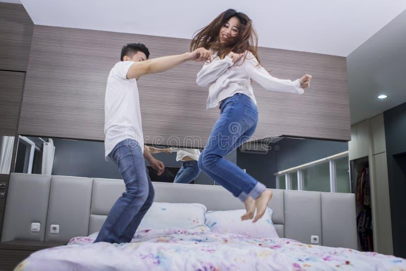 Εύθυμο ζεύγος που πηδά μαζί στο κρεβάτι στοκ φωτογραφίες