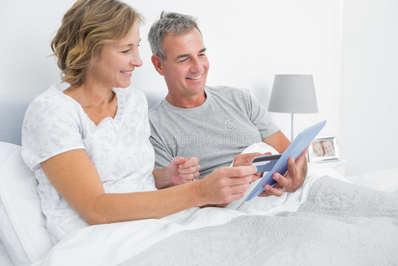 Εύθυμο ζεύγος που χρησιμοποιεί το PC ταμπλετών τους που αγοράζει on-line στοκ φωτογραφία με δικαίωμα ελεύθερης χρήσης