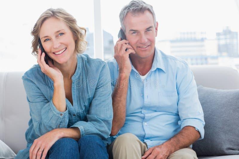 Εύθυμο ζεύγος στα κινητά τηλέφωνά τους στον καναπέ στοκ φωτογραφίες