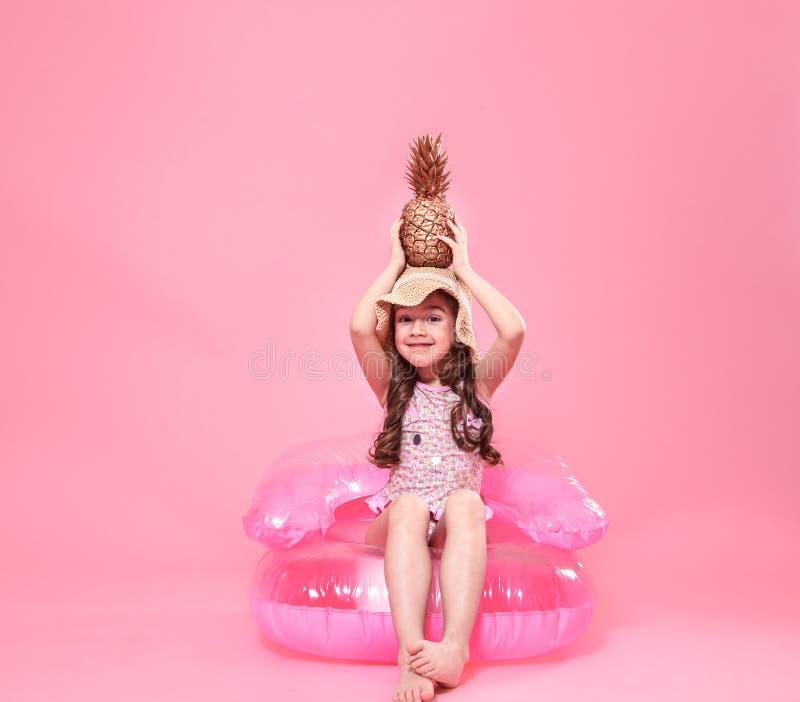 Εύθυμο θερινό κορίτσι με τον ανανά στο χρωματισμένο υπόβαθρο στοκ φωτογραφία
