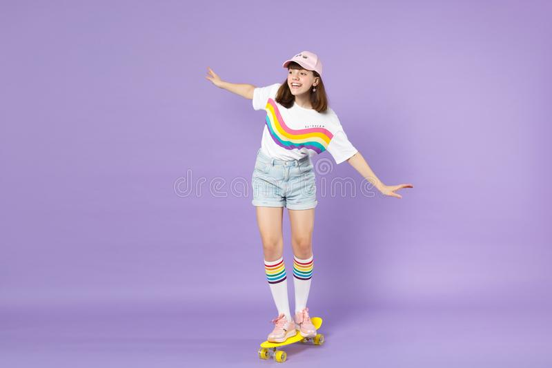 Εύθυμο κορίτσι εφήβων στα ζωηρά ενδύματα που οδηγούν τα κίτρινα skateboard χέρια διάδοσης που φαίνονται κατά μέρος απομονωμένα στ στοκ φωτογραφία με δικαίωμα ελεύθερης χρήσης