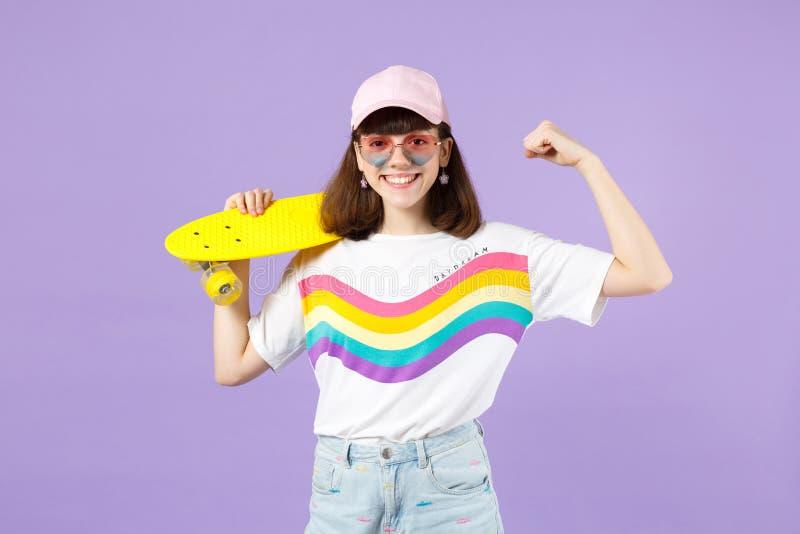 Εύθυμο κορίτσι εφήβων στα ζωηρά ενδύματα, eyeglasses που κρατά κίτρινο skateboard, που παρουσιάζει δικέφαλους μυς, μυ'ες που απομ στοκ φωτογραφία