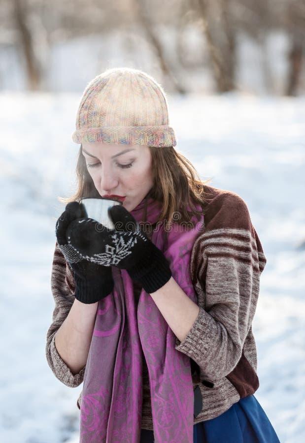 Εύθυμο κορίτσι που πίνει το καυτό τσάι με τον ατμό υπαίθριο στοκ εικόνες