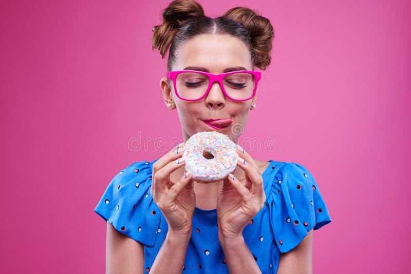 Εύθυμο κορίτσι που τρώει doughnut και που γλείφει τα χείλια στοκ φωτογραφίες