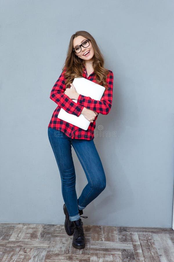 Εύθυμο κορίτσι στα γυαλιά που θέτουν και που χαμογελούν αγκαλιάζοντας το lap-top στοκ φωτογραφία