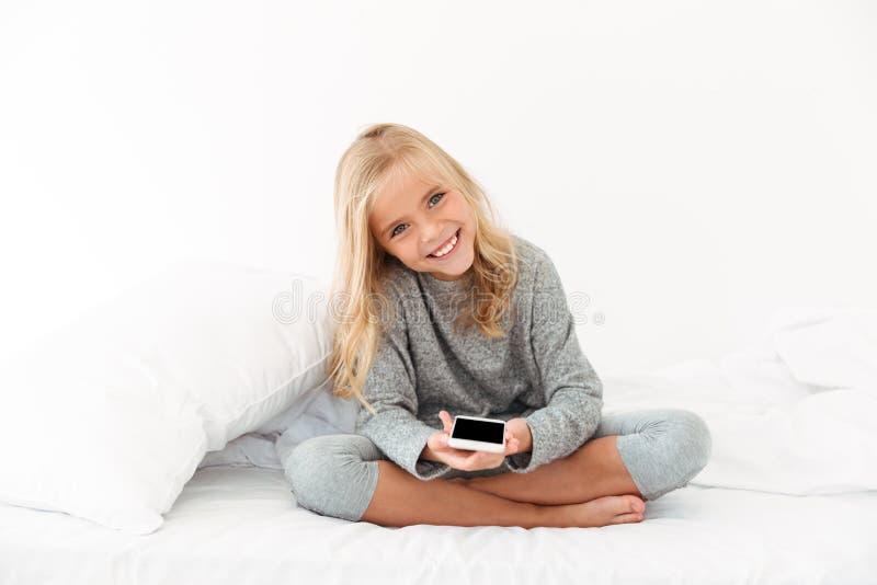 Εύθυμο κορίτσι στις γκρίζες πυτζάμες που κρατά το smartphone, που εξετάζει το έκκεντρο στοκ φωτογραφία