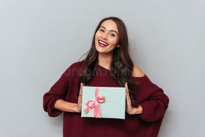 Εύθυμο κορίτσι brunette στο μοντέρνο πλεκτό δώρο β εκμετάλλευσης πουλόβερ στοκ εικόνες