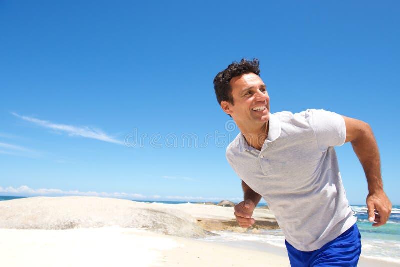 Εύθυμο μέσο ηλικίας άτομο που τρέχει στην παραλία στοκ εικόνες