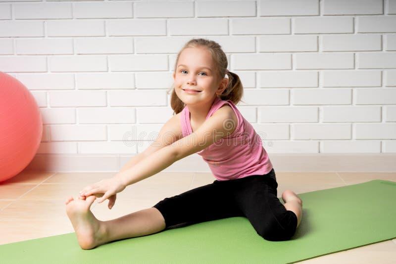 Εύθυμο μικρό κορίτσι που κάνει τις αθλητικές ασκήσεις στο χαλί στο σπίτι, τον αθλητισμό των παιδιών και τη γιόγκα στοκ φωτογραφία