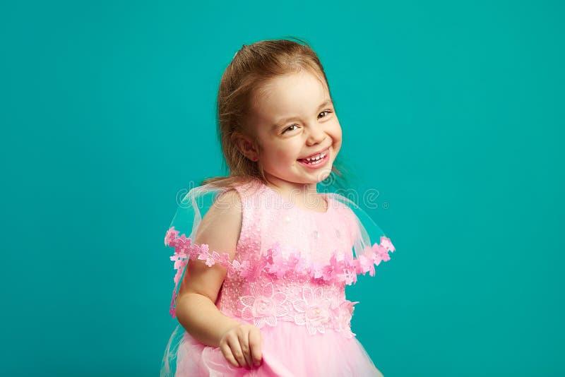 Εύθυμο μικρό κορίτσι στο όμορφο ρόδινο φόρεμα στοκ εικόνα