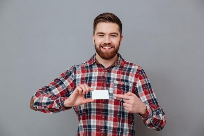 Εύθυμο νέο γενειοφόρο άτομο με τη επαγγελματική κάρτα copyspace στοκ φωτογραφίες με δικαίωμα ελεύθερης χρήσης