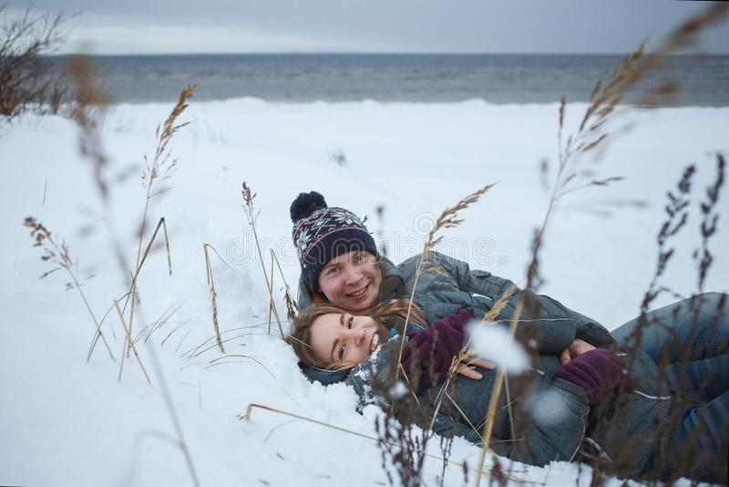 Εύθυμο νέο ζεύγος που βρίσκεται στο χιόνι κοντά στην παραλία SE Χειμερινές romanctic διακοπές στοκ εικόνες