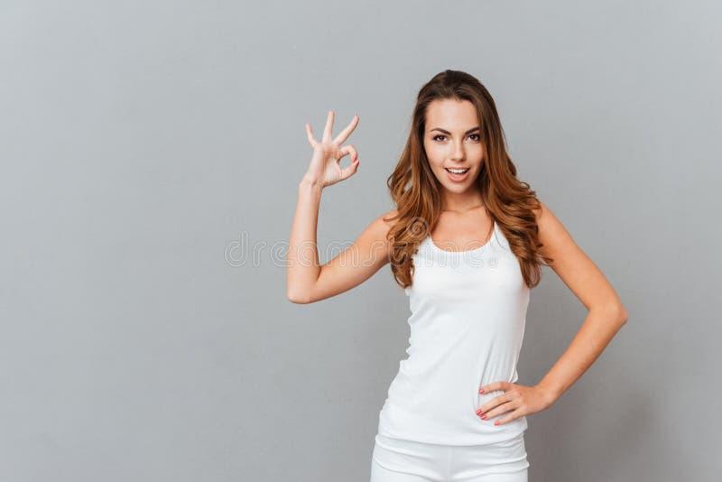 Εύθυμο νέο κορίτσι που παρουσιάζει εντάξει σημάδι με τα δάχτυλα στοκ εικόνα