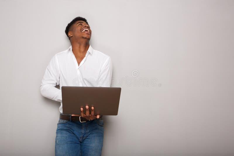 Εύθυμο νέο lap-top εκμετάλλευσης ατόμων αφροαμερικάνων και να ανατρέξει  στοκ φωτογραφία με δικαίωμα ελεύθερης χρήσης