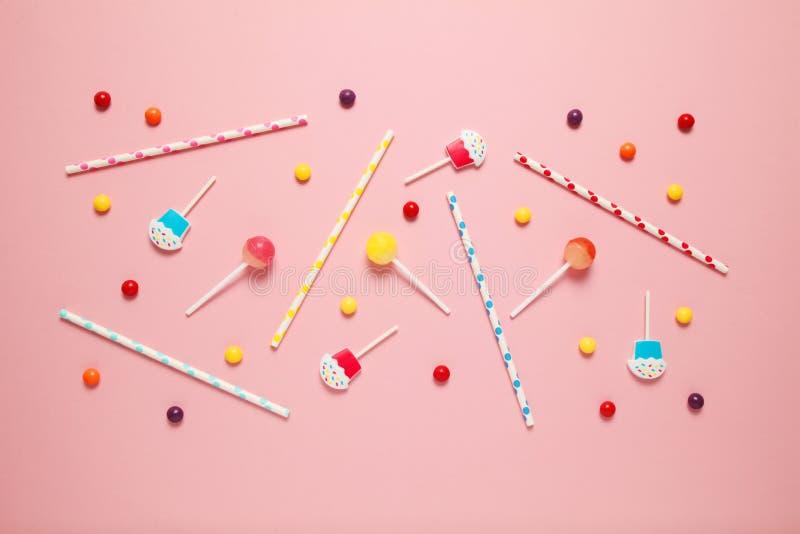 Εύθυμο ντεκόρ παιδιών για ένα κόμμα, ρόδινο υπόβαθρο Γλυκές καραμέλες, φωτεινές σφαίρες, εορταστικά κεριά και άχυρα στοκ εικόνα με δικαίωμα ελεύθερης χρήσης