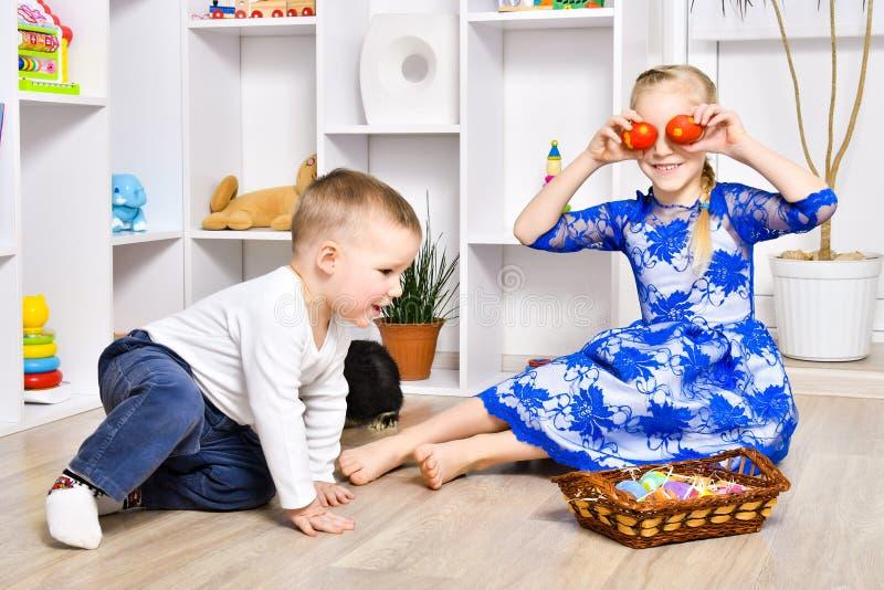 Εύθυμο παιχνίδι αδελφών και αδελφών στο Πάσχα στοκ εικόνες με δικαίωμα ελεύθερης χρήσης