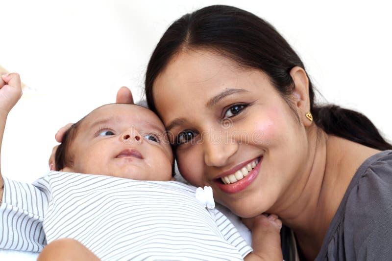 Εύθυμο παιχνίδι μητέρων με νεογέννητο στοκ φωτογραφία