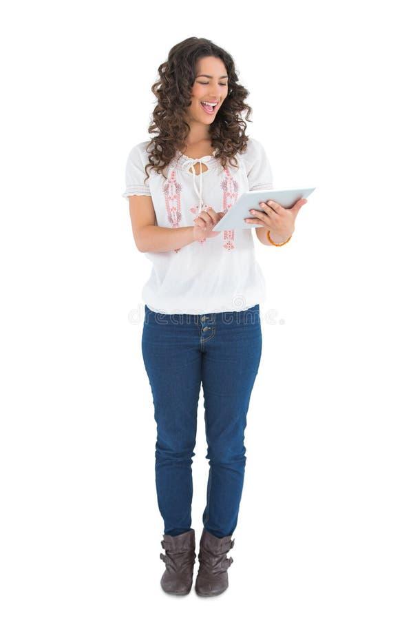 Εύθυμο περιστασιακό brunette χρησιμοποιώντας το PC ταμπλετών της στοκ φωτογραφία