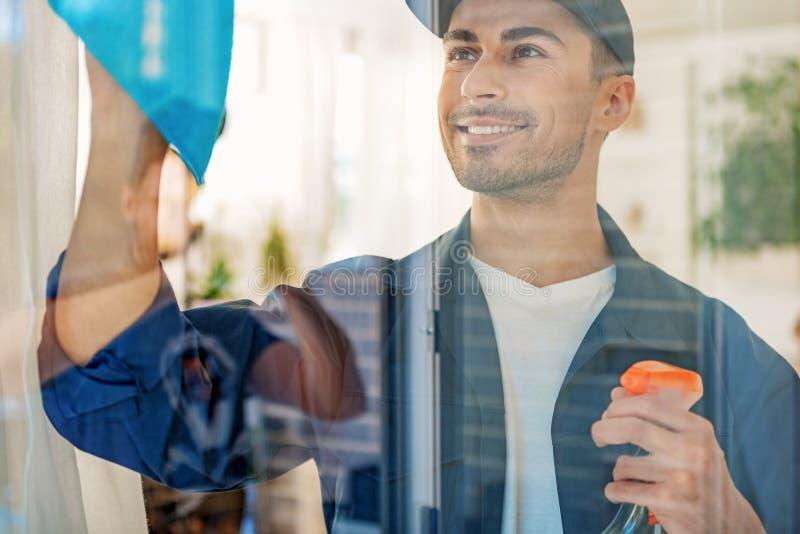 Εύθυμο συγκεντρωμένο καθαρίζοντας γυαλί ατόμων στοκ εικόνες με δικαίωμα ελεύθερης χρήσης