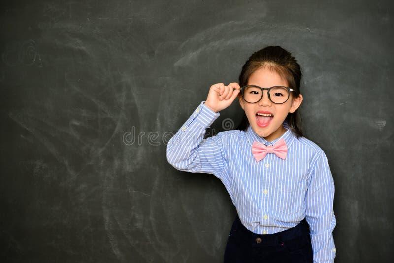 Εύθυμο φόρεμα μικρών κοριτσιών επάνω στο δάσκαλο σχολείου στοκ φωτογραφία