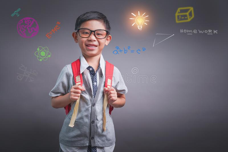 Εύθυμο χαμογελώντας μικρό παιδί με το μεγάλο σακίδιο πλάτης Εξέταση τη κάμερα Σχολική έννοια o στοκ εικόνα