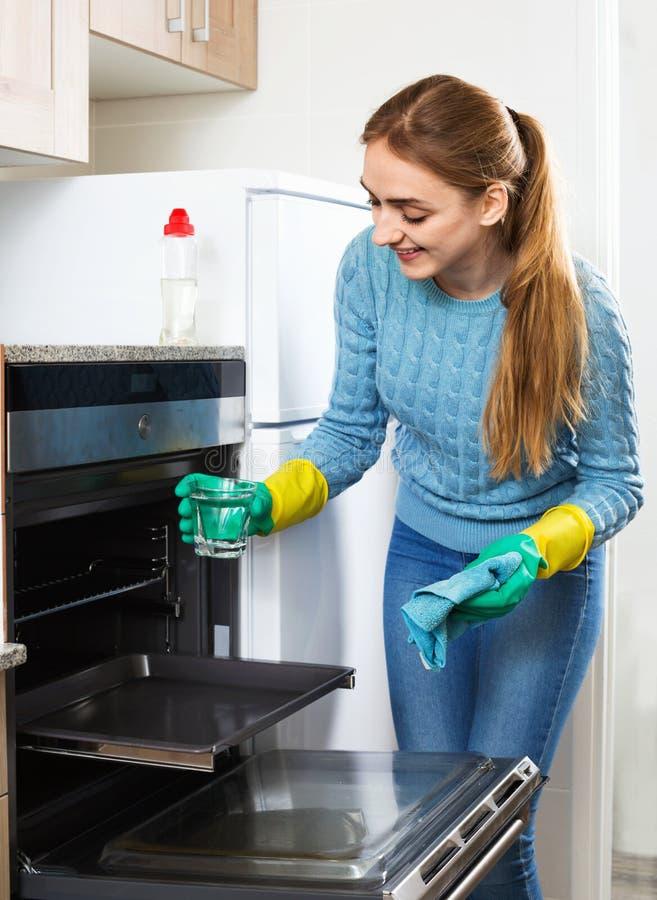 Εύθυμο χαμογελώντας ευτυχές ενήλικο κορίτσι που αφαιρεί τον ταμπάκο στο φούρνο στοκ εικόνα
