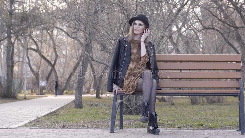 Εύθυμο όμορφο κορίτσι στη συνεδρίαση καπέλων στον πάγκο στο ηλιόλουστο πάρκο φθινοπώρου r Όμορφη νέα γυναίκα στη συνεδρίαση καπέλ στοκ φωτογραφία με δικαίωμα ελεύθερης χρήσης