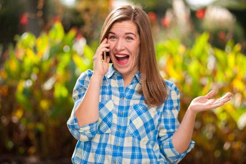 Εύθυμο όμορφο νέο κορίτσι που μιλά στο τηλέφωνο στοκ φωτογραφίες