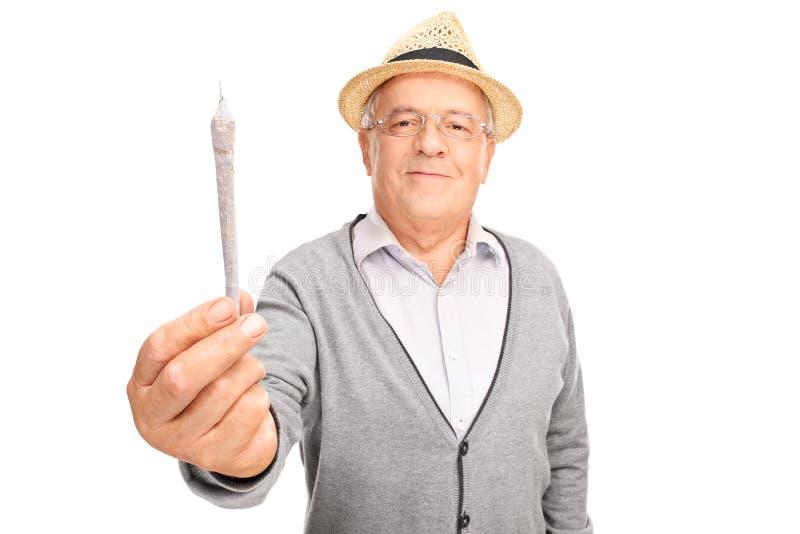 Εύθυμο ώριμο άτομο που κρατά την ιατρική μαριχουάνα στοκ εικόνα με δικαίωμα ελεύθερης χρήσης